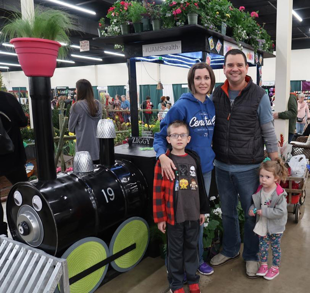 Mother, Father, a boy and a girl standing next to garden train.