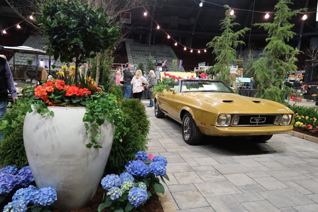 Picture of show floor with a car full of flowers.